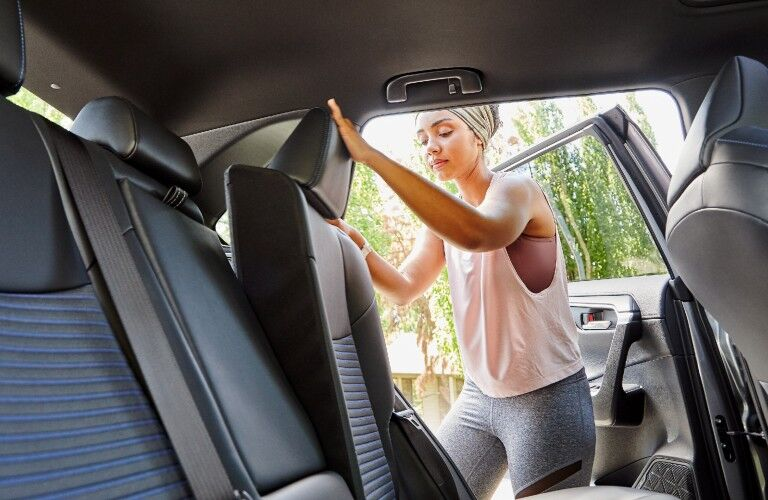A photo of a person folding down the rear seats in the 2021 Toyota RAV4.