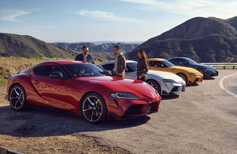 2020 Toyota GR Supra with people standing beside a red one