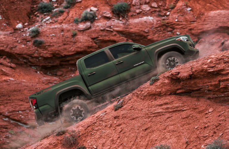 A photo of the 2021 Toyota Tacoma climbing a desert hill.