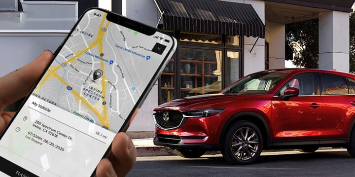Cell phone in hand with Mazda vehicle in the background