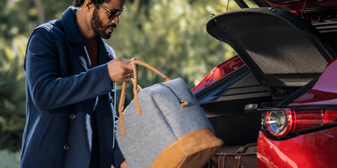 Man putting tote bag into the trunk