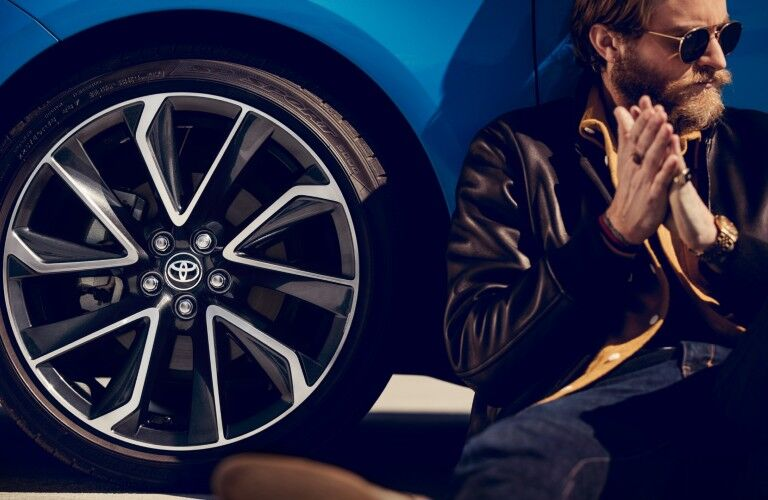 man by the wheel of the 2020 Toyota Corolla Hatchback