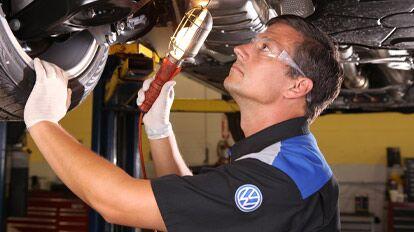 Man servicing and maintaining Volkswagen model at Highland Volkswagen