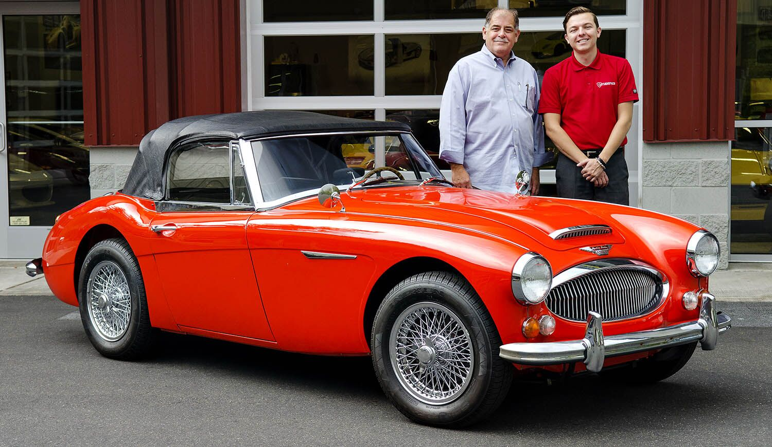 Two gentleman outside Cats Exotics exotic car dealership beside a red Austin-Healey