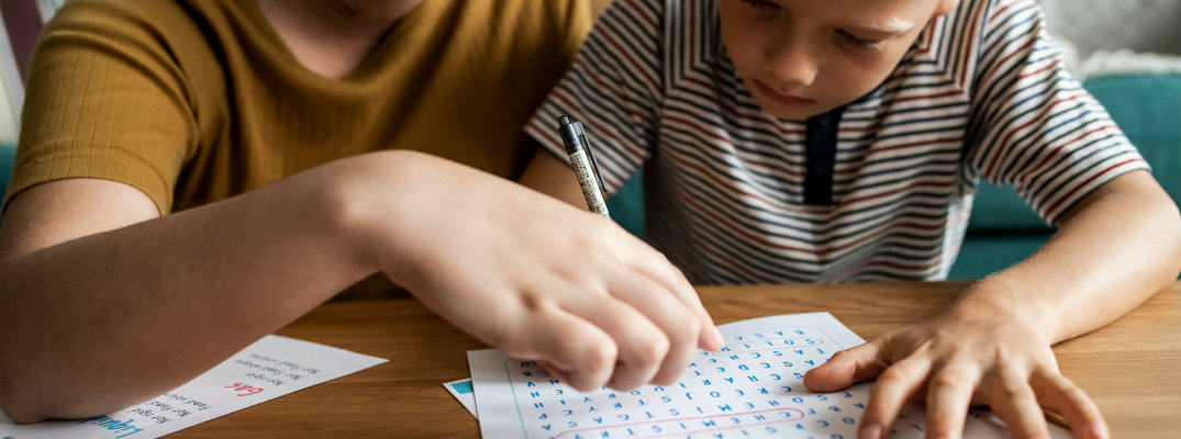 Young boy and parent working on a word search