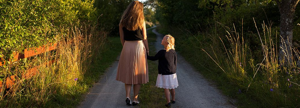 mom and daughter holding hands walking on a forest trail