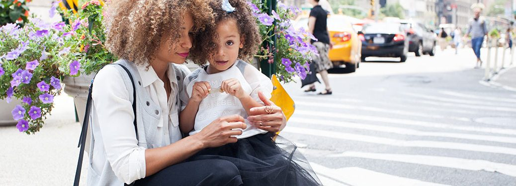 Image of a woman and her daughter crouched near flowers on a city sidewalk