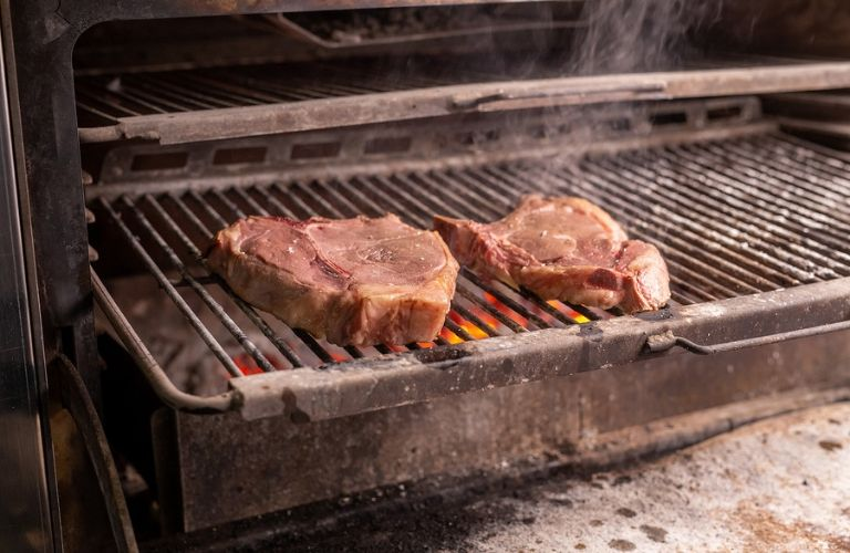 Image of two steaks cooking on a grill
