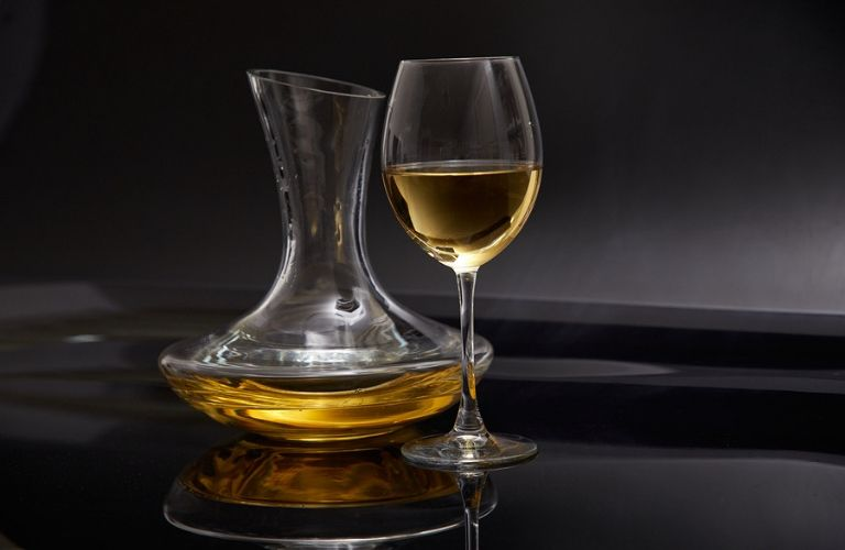 Image of a wine decanter and wine glass with wine in them on a table