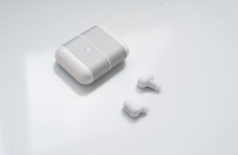 Image of wireless earbuds and their charging case placed on a white table