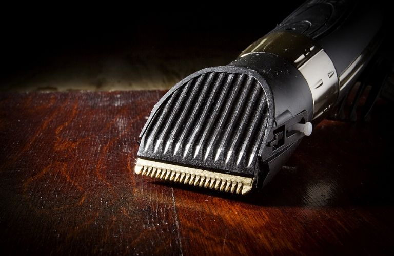 Closeup of an electric razor placed on a wood table