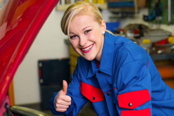 Pretty blonder Service Mechanic Smiling and Giving Thumbs Up While Working on a Car