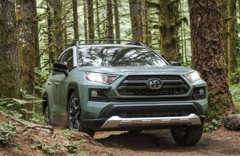 The front view of a green 2021 Toyota RAV4 driving off-road.