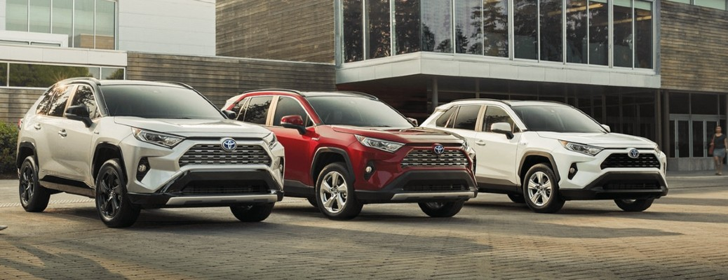 A lineup of a gray, a red, and a white 2021 Toyota RAV4 Hybrid models parked in front of a building.