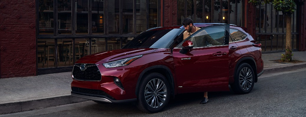A man getting into the front of a red 2021 Toyota Highlander.
