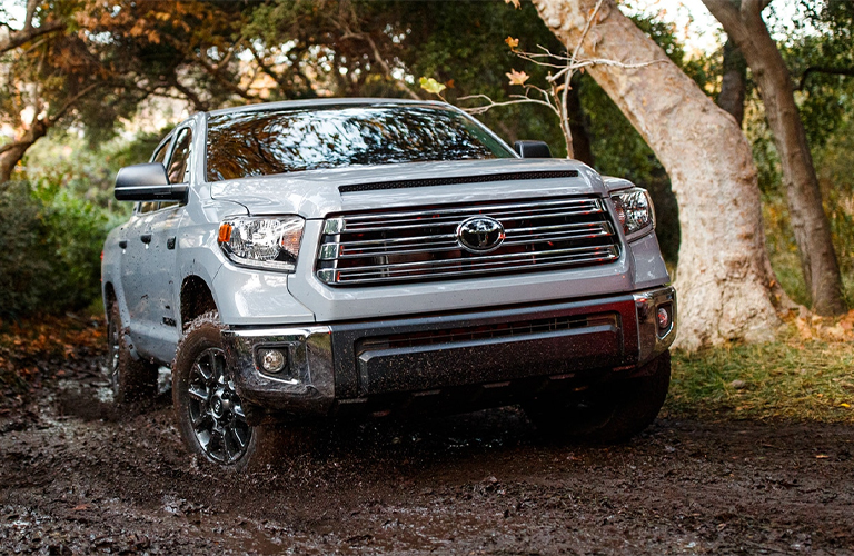 The front of a silver 2021 Toyota Tundra driving through mud.