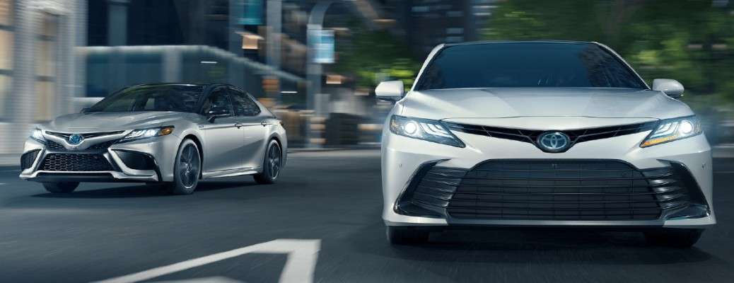 Two 2021 Toyota Camry's side by side driving on road