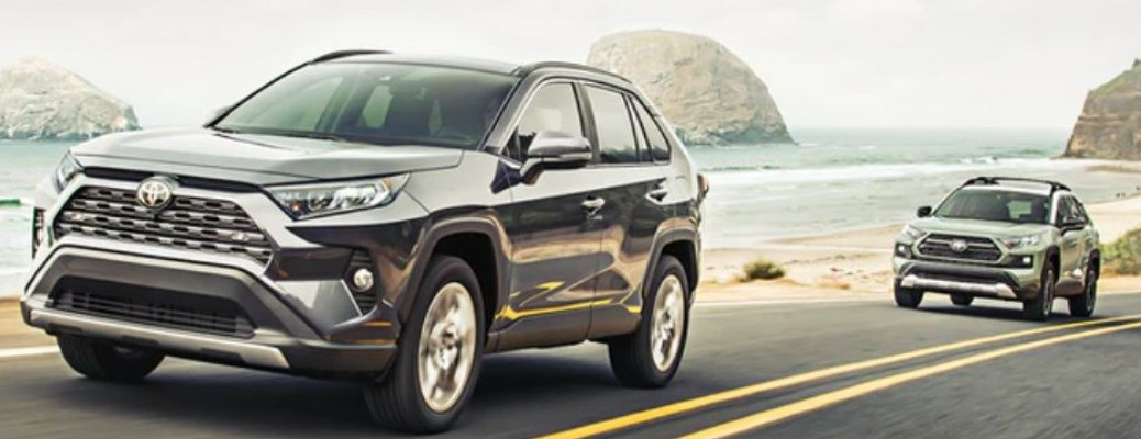 Two 2021 Rav4's driving on road by beach