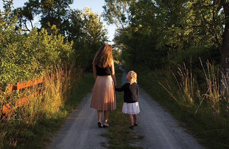Mother and daughter walking down trail