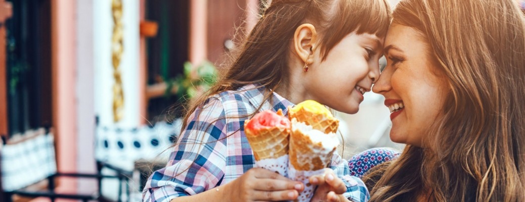 Mother and daughter eating ice cream and smiling