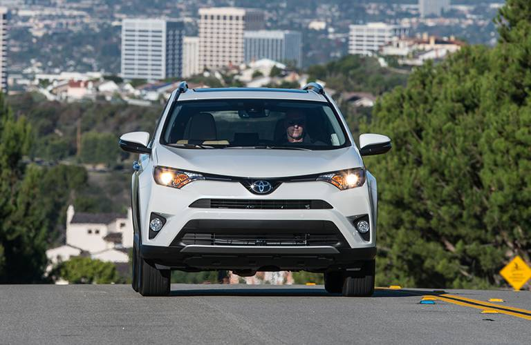The front side of a white 2016 Toyota RAV4 driving away from a city.