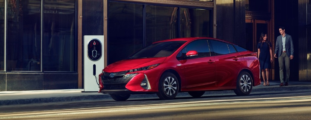 A couple walking towards a red 2021 Toyota Prius Prime that is charging.