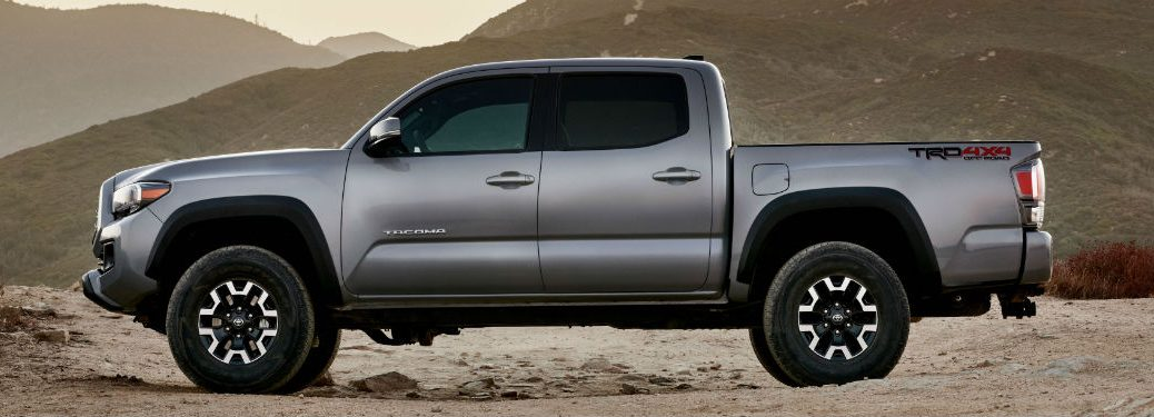2020 Toyota Tacoma exterior driver side profile on dusty lot with mountain background