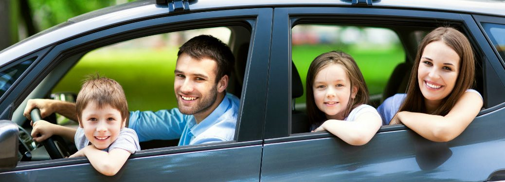 Happy family sitting in car leaning out windows
