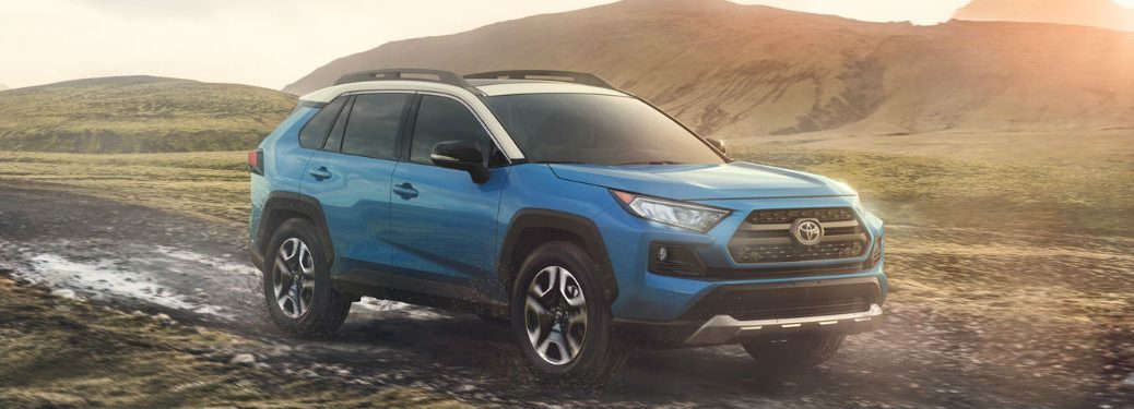 2019 Toyota RAV4 exterior front fascia and passenger side off road with hills and sunrise