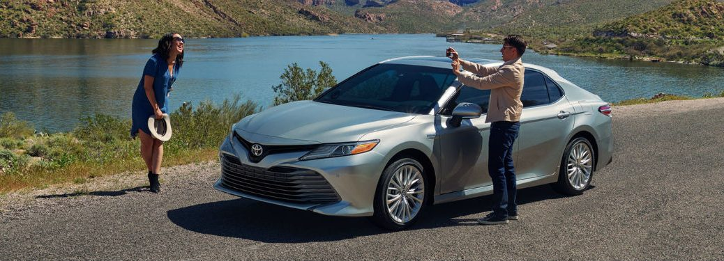 2019 Toyota Camry exterior front fascia and drivers side man taking photo of woman at lakeside
