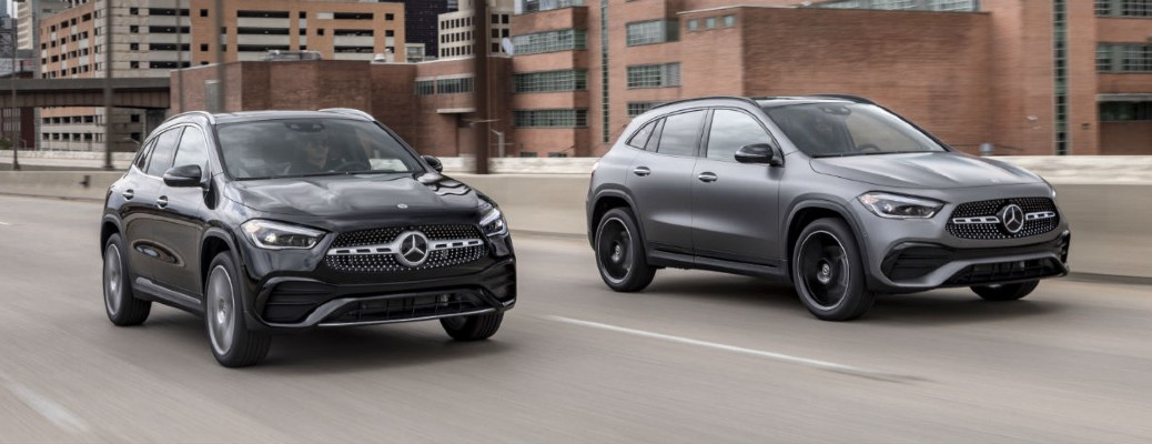 One black and one gray 2021 Mercedes-Benz GLA models driving down a city road.