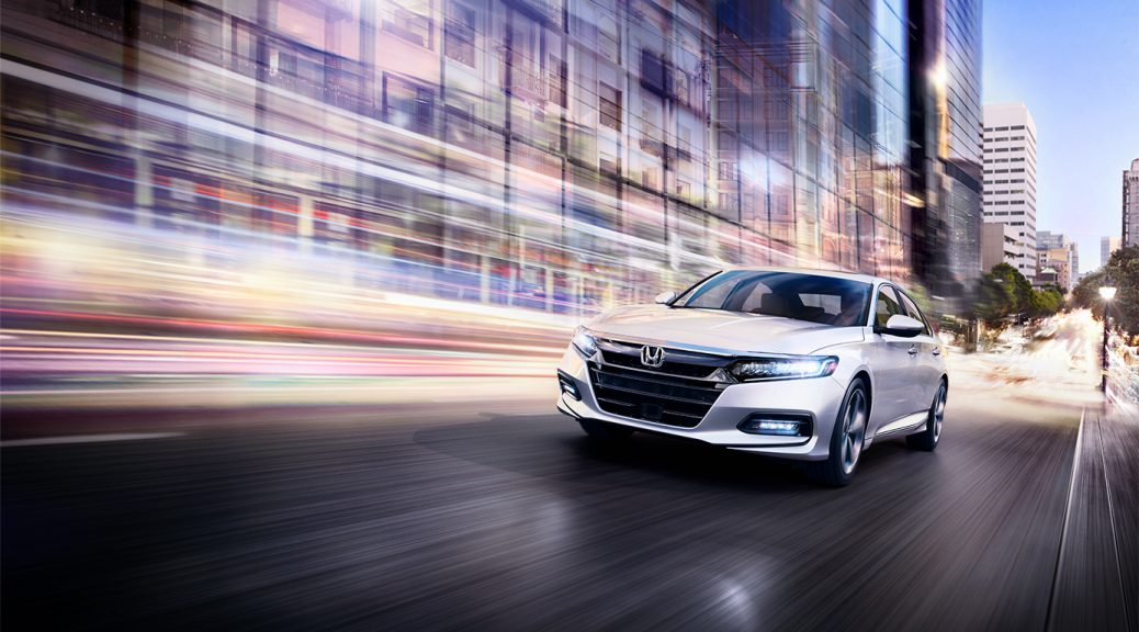 Image of a white 2019 honda Accord driving on a city street at night.