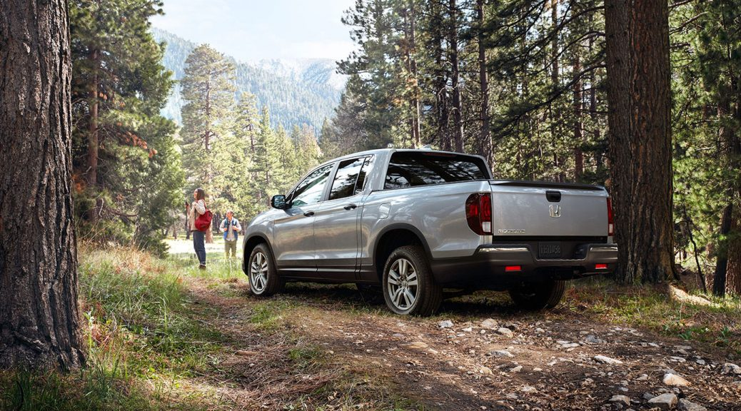 Image of a silver 2019 Honda Ridgeline parked in the woods.