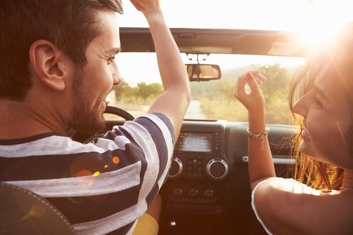 Image of a young couple driving into the sunset in a convertible.