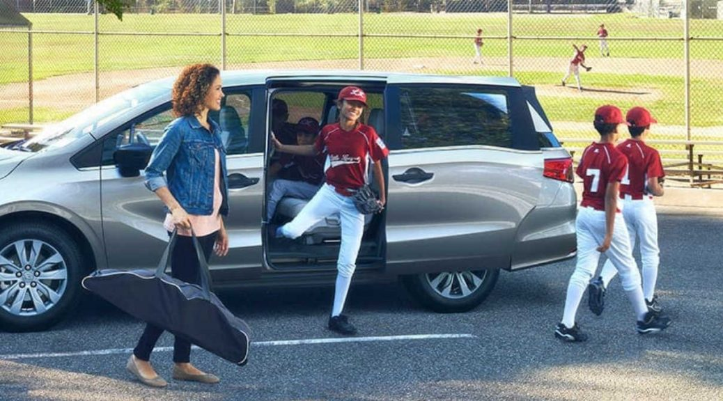 Image of a group of kids in baseball uniforms entering a Honda Odyssey.