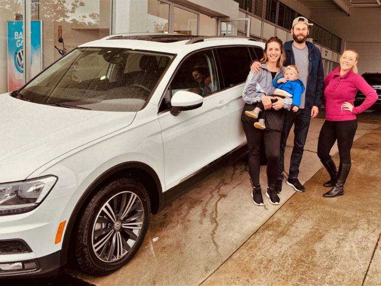 family standing next to a white 2019 VW Tiguan