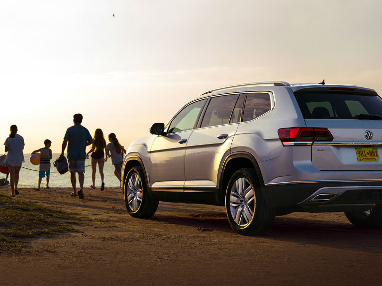 family walking toward the beach from their 2019 VW Atlas