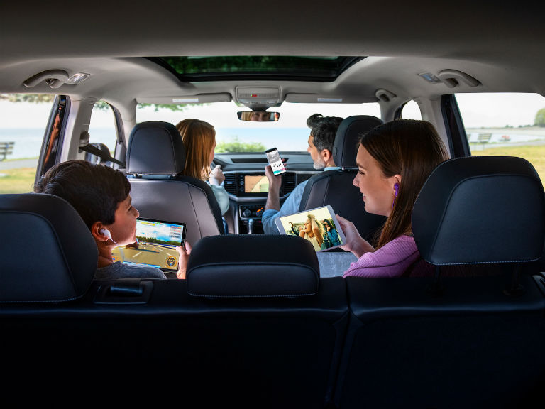 family on their phones in an SUV