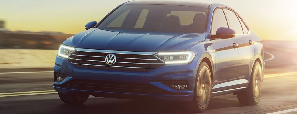 Front view of blue 2019 VW Jetta with LED headlights illuminated