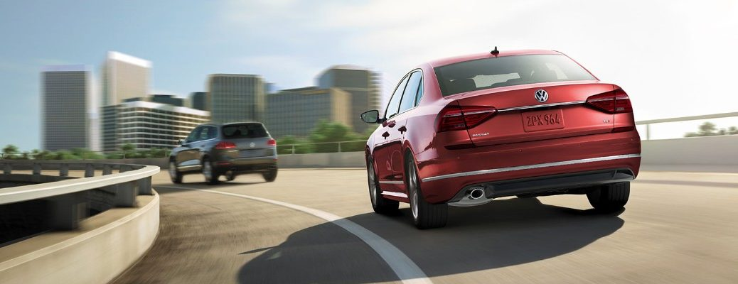 Rear view of red 2019 VW Passat driving over bridge behind Volkswagen model