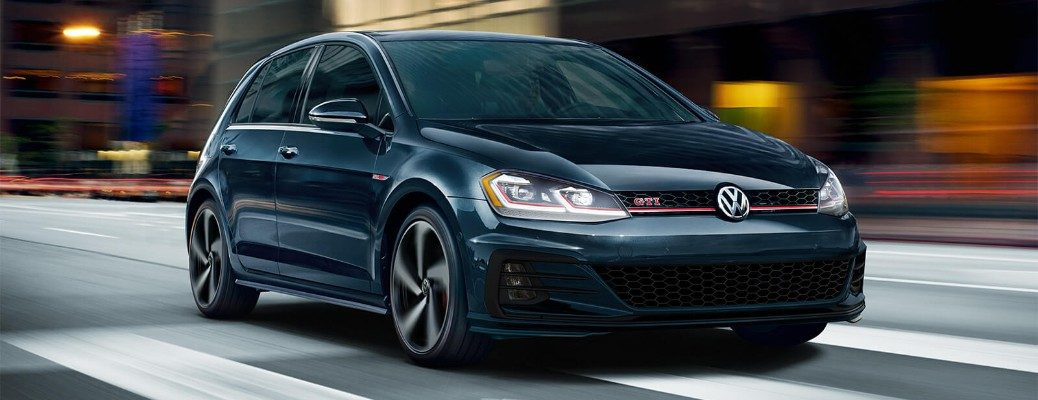 Front view of blue 2019 Volkswagen Golf GTI driving through city