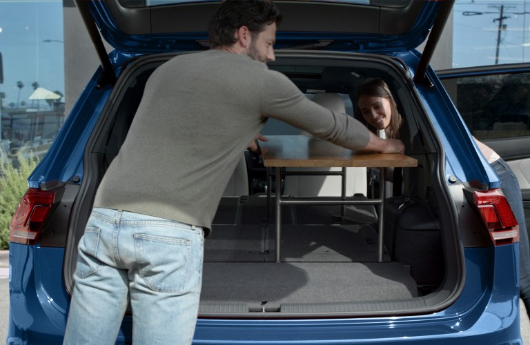 Man storing cargo in rear area of 2020 VW Tiguan