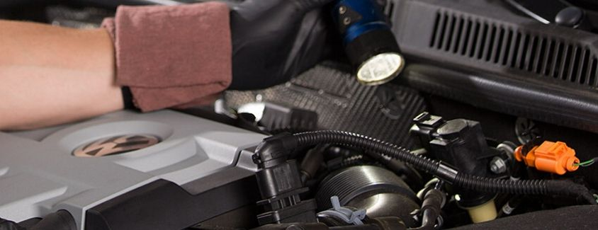 Image of a service technician examining a vehicle's engine