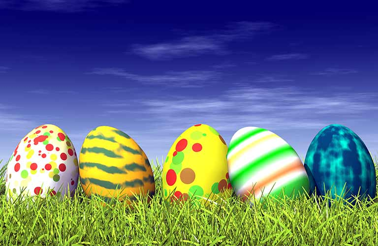 Image of a row of decorated Easter eggs sitting in the grass
