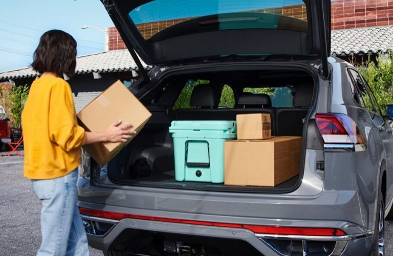Image of a woman loading the cargo area of a gray 2020 Volkswagen Atlas Cross Sport
