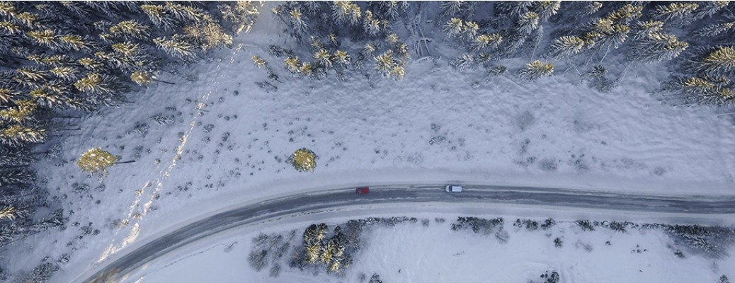 Long curved road with two cars driving on it with snow on either side