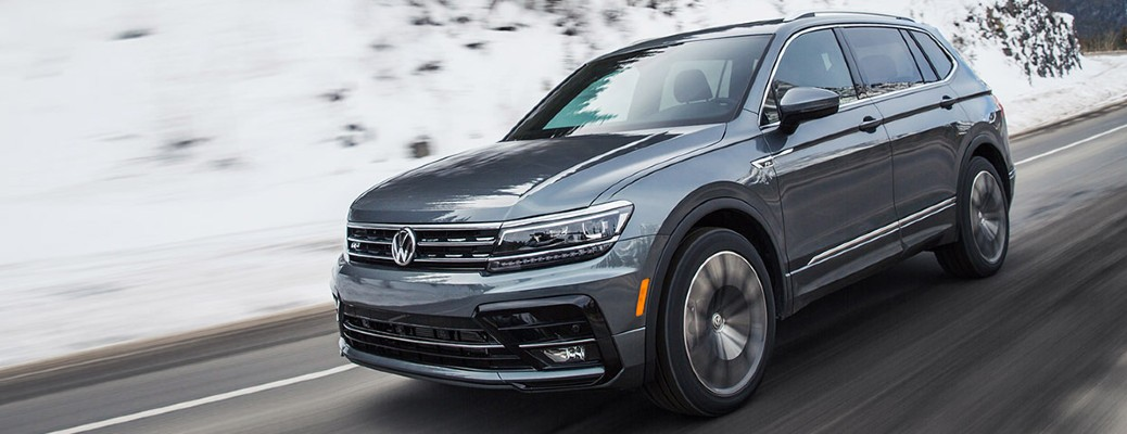 A 2021 Volkwagen Tiguan driving on a road with snow in the background