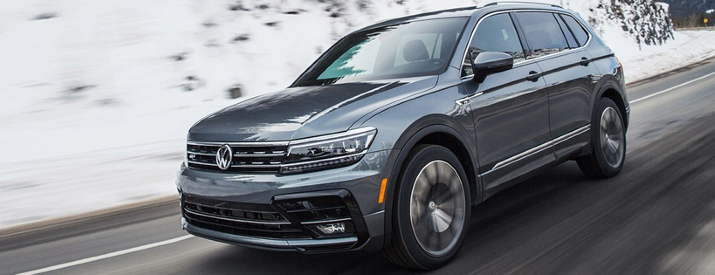 A 2021 Volkswagen Tiguan driving on a road with snow in the background