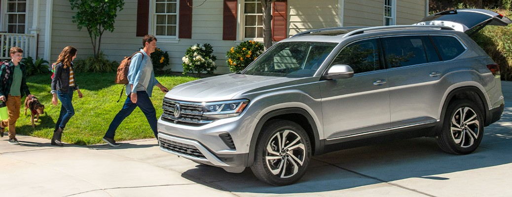 A family of three walking toward a 2021 Volkswagen Atlas that is parked in a driveway by a house