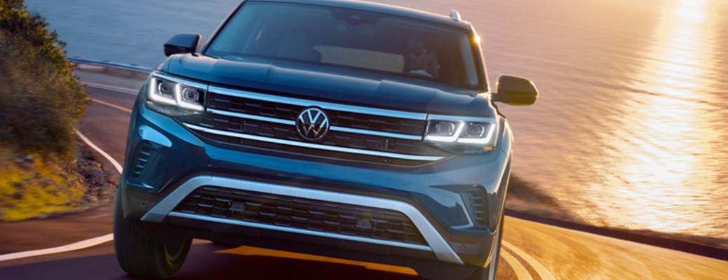A 2021 Volkswagen Atlas driving on a road with a body of water in the background